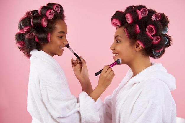 Mãe negra e menina pintam uns aos outros.