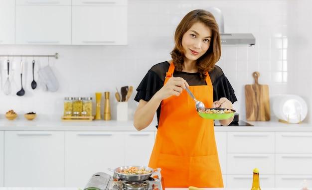 Mãe no avental laranja na cozinha em casa feliz, sorria e orgulho com comida na colher, ela pegando da panela voadora como sucesso para aprender a cozinhar em família para a criança.