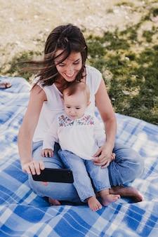 Mãe nova e bebê feliz que usam o telefone móvel ao ar livre. conceito de tecnologia
