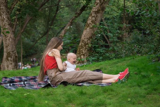 Mãe nova e criança que sentam-se em um parque em uma manta de piquenique. fim de semana com a criança ao ar livre