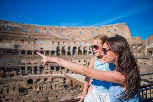 Mãe nova e menina que abraçam no coliseu, roma, itália.