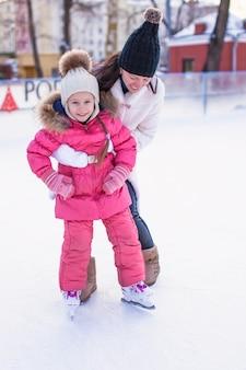 Mãe nova e sua filha pequena bonito em uma pista de patinagem