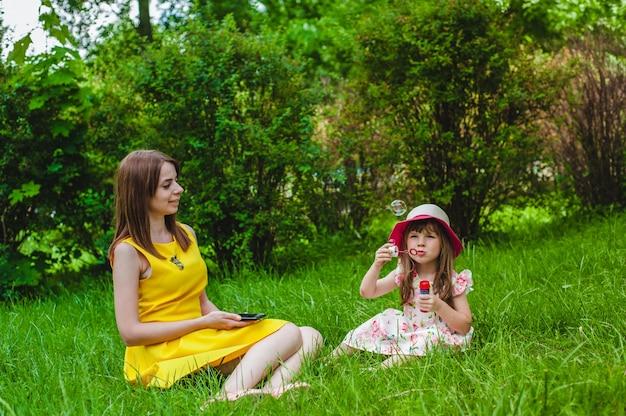 Mãe observando como sua filha funde bolhas de sabão