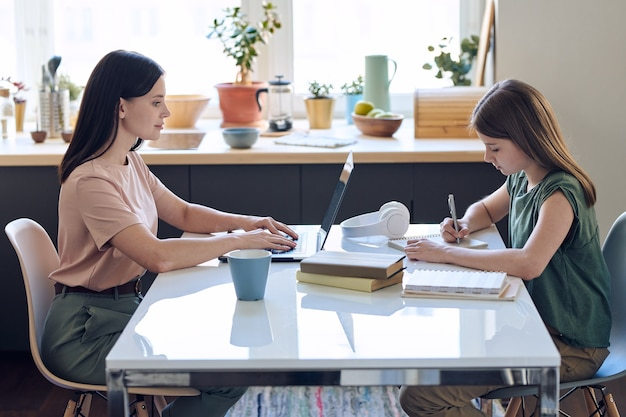Mãe ocupada de meia-idade digitando no laptop enquanto a filha fazendo o dever de casa em uma mesa com ela