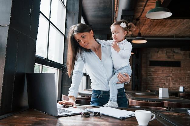 Mãe ocupada. mulher de negócios com roupa oficial com criança está dentro de casa no café durante o dia.