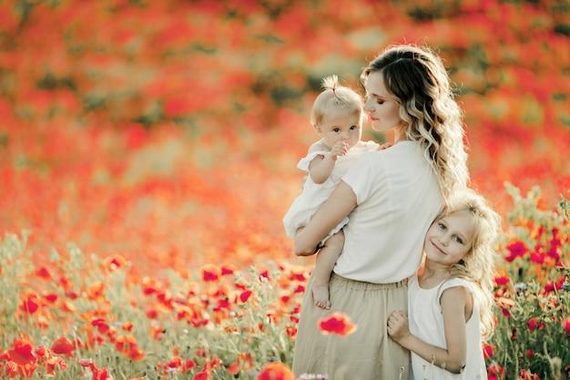 Mãe olha para o bebê, filha mais velha se aninha a mãe no campo de papoulas