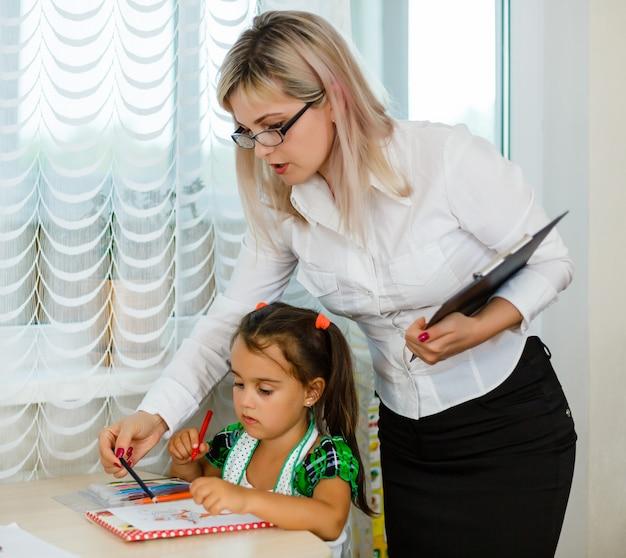 Mãe olhando como sua filha criança desenhando uma imagem