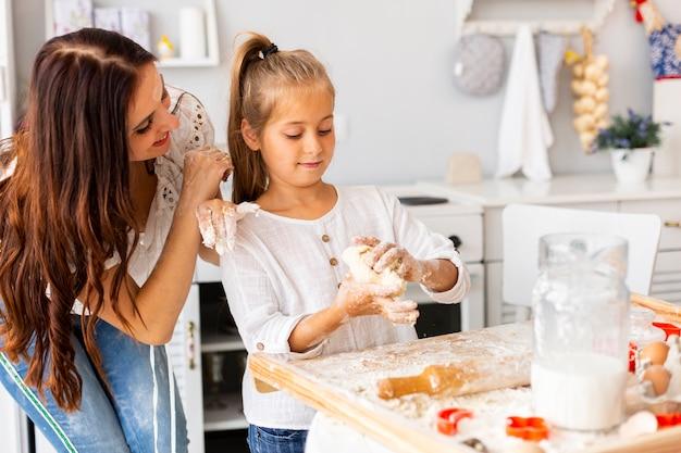 Mãe olhando para a filha cozinhar