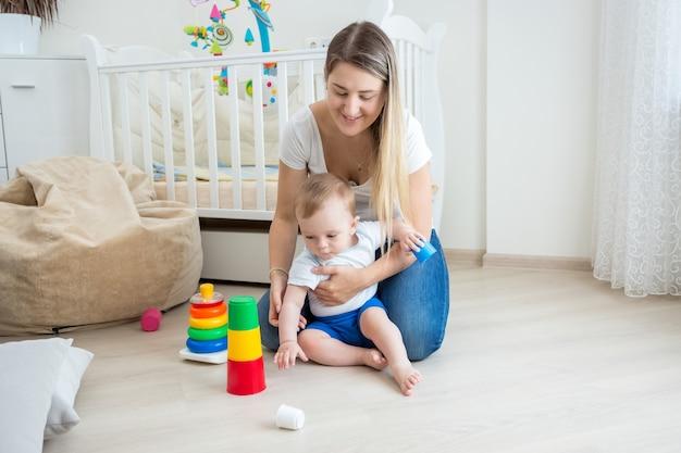 Mãe olhando para o filho montando pirâmide de brinquedo no chão da sala de estar