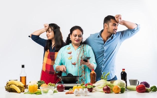 Mãe ou irmã indiana ativa fazendo chão para filho e filha na cozinha
