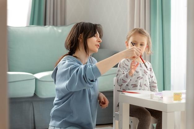 Mãe ou professora de arte está ensinando a criança a desenhar e segurar o pincel corretamente