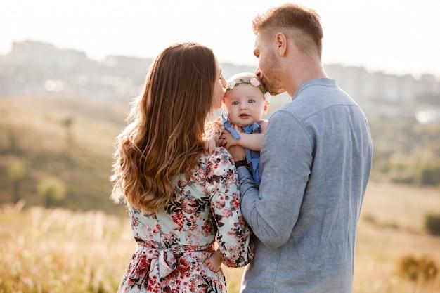 Mãe, pai beijando sua pequena mulher num dia de verão. dia da mãe, do pai e do bebê. família feliz para passear fora da cidade.