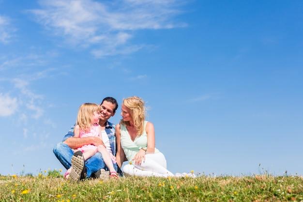 Mãe, pai, criança, sentando, ao ar livre