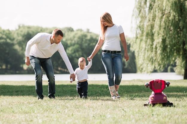 Mãe, pai e brincar com o filho pequeno para passear no parque de verão