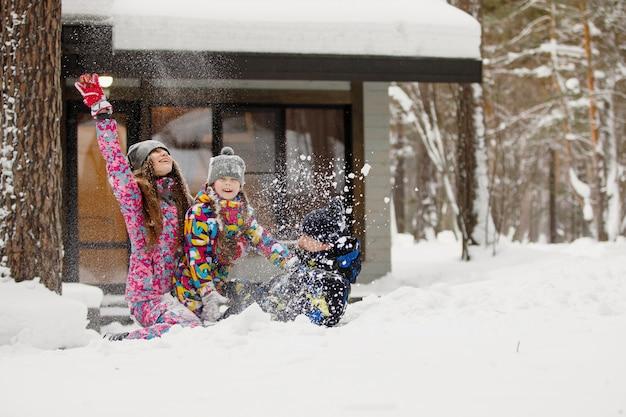 Mãe, pai e filha da família se divertem e brincam com neve na floresta de inverno perto de casa.