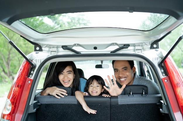 Mãe, pai e filha dentro de um carro olham pela janela traseira