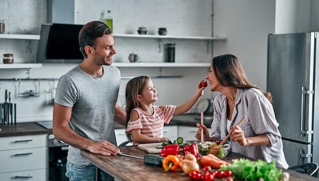 Mãe, pai e filha estão cozinhando na cozinha. conceito de família feliz. homem bonito, mulher jovem e atraente e sua filha pequena estão fazendo salada juntos. estilo de vida saudável.