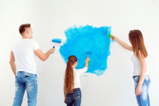 Mãe, pai e filha pintando a parede em sua nova casa.