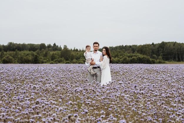 Mãe, pai e filho no fundo de um campo roxo florescendo
