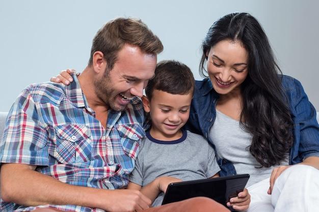 Mãe, pai e filho olhando para tablet digital