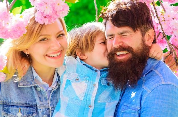Mãe, pai e filho pequeno juntos no parque de sakura florescendo. família de turista andar no jardim primavera.