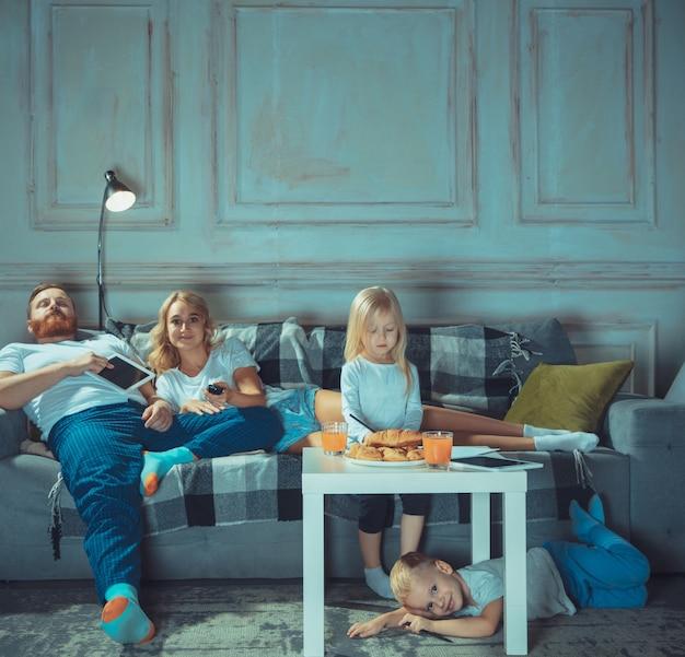 Mãe pai e filhos em casa se divertindo, conforto e conceito aconchegante
