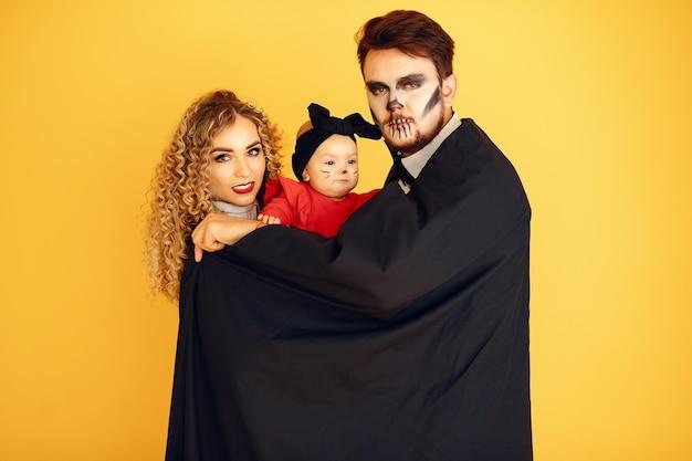 Mãe, pai e filhos em fantasias e maquiagem. pessoas de pé sobre um fundo amarelo.