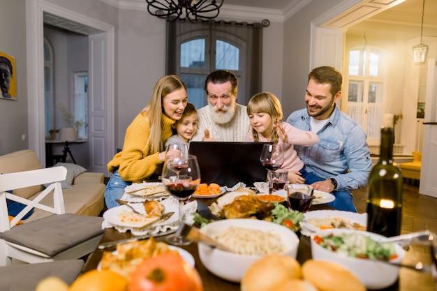 Mãe, pai e filhos pequenos, avô jantam nas férias, sentados à mesa na sala aconchegante, usando o laptop e conversando