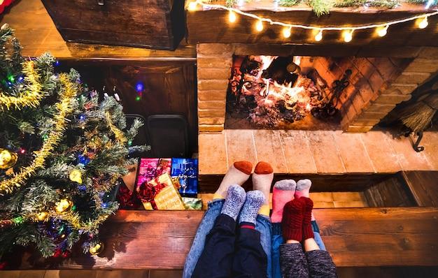 Mãe, pai e filhos sentados perto de uma lareira aconchegante no inverno