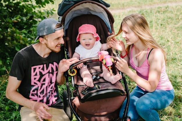 Mãe, pai e menina andando com seu bebê e carrega-o em um lindo carrinho de bebê