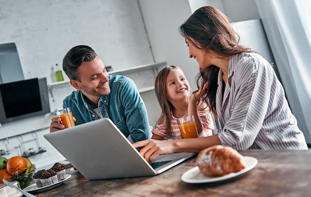 Mãe, pai e sua linda filha tomam café da manhã na cozinha usando laptop e conversam. conceito de família feliz.