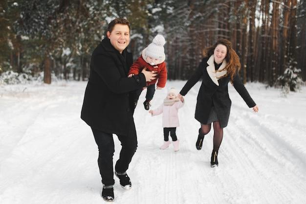 Mãe, pai, filha e filho se divertindo na floresta de inverno. pais ativos com filhos correm na floresta de neve