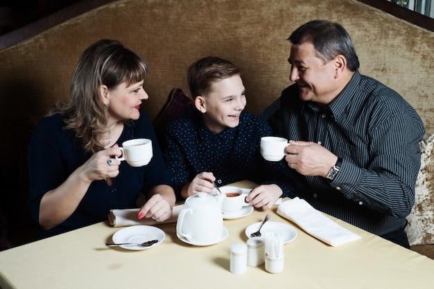 Mãe, pai, filho bebem chá