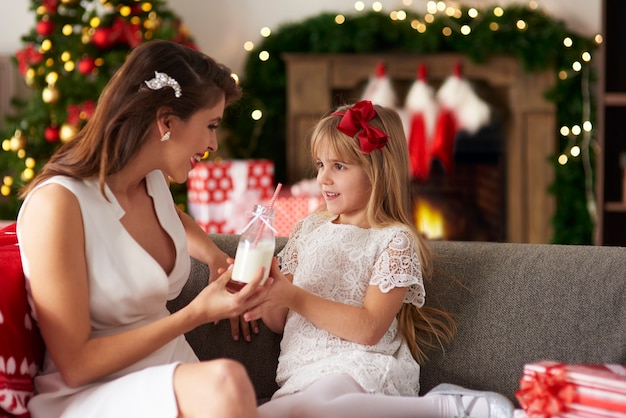 Mãe passando mamadeira de leite para filha