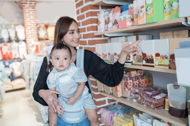 Mãe pegando algum produto na loja de bebês enquanto carregava seu filho