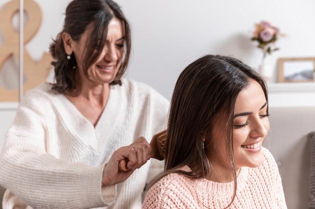 Mãe, penteando o cabelo da filha