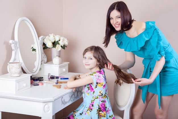 Mãe penteando sua linda filha pré-adolescente