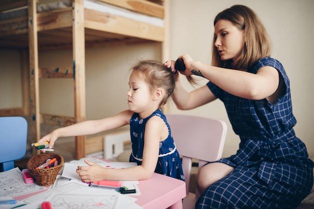 Mãe penteia a filha e arruma o cabelo.