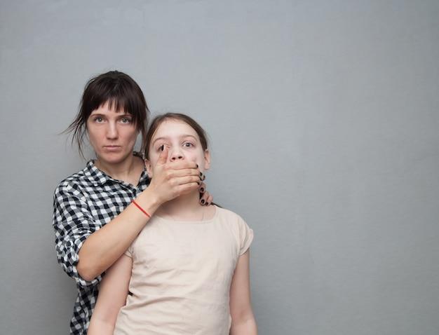 Mãe perturbada dos anos 30 fechando a boca do filho. problemas de relações entre pais e filhos
