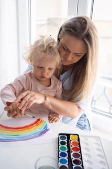 Mãe pintando com criança em casa