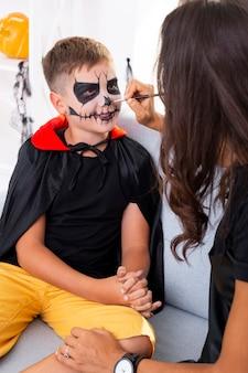 Mãe pintando o rosto de seus filhos para o halloween