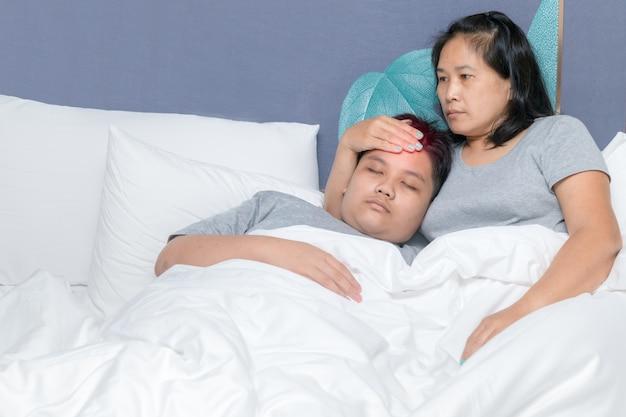 Mãe põe a mão na testa para medir a temperatura do filho na cama.