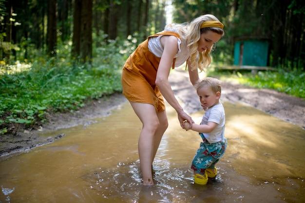 Mãe preocupada posando com o filho em uma poça na floresta