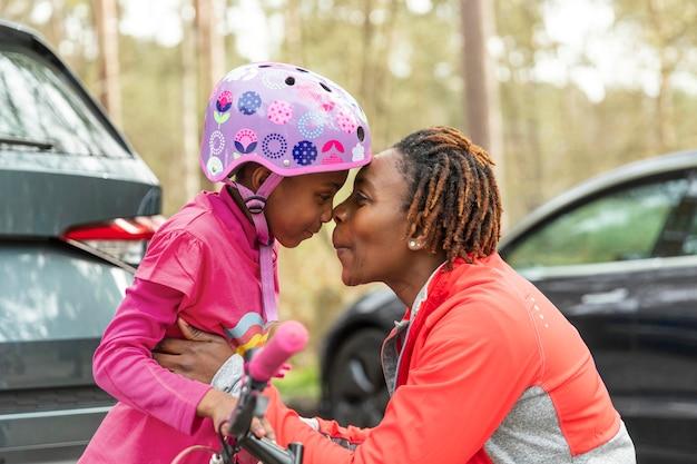 Mãe preparando a filha para um passeio de bicicleta