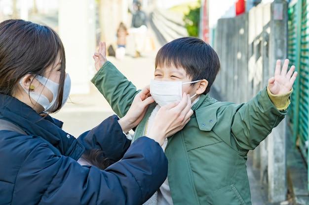 Mãe preparando a máscara de seu filho em trânsito