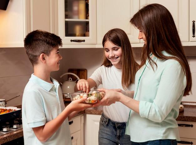 Mãe preparando comida na cozinha com crianças