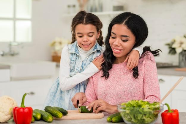 Mãe preparando comida para a filha