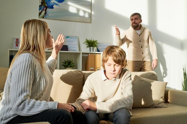 Mãe protegendo o filho e gritando com o marido