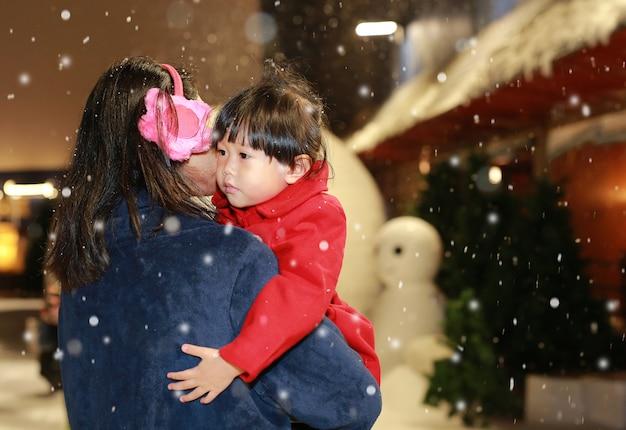 Mãe que leva a menina adorável na neve, tempo de inverno.