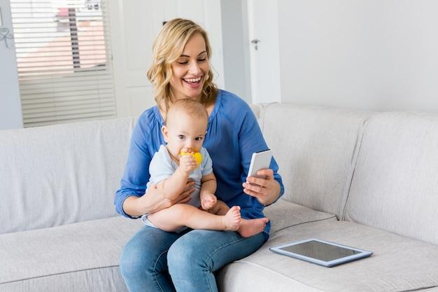 Mãe que prende o bebé e usando telefone celular na sala de estar